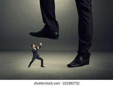 concept photo of conflict between subordinate and boss. angry young businessman showing fist and looking up at big boss. photo in the dark room