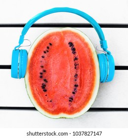 concept photo of a cut watermelon with headphones, a bright image for a music album, a summer delight with a tropical sounding mood