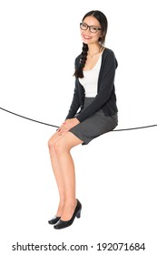 Concept photo of full body Asian business woman, seated on a thin rope isolated white background.
