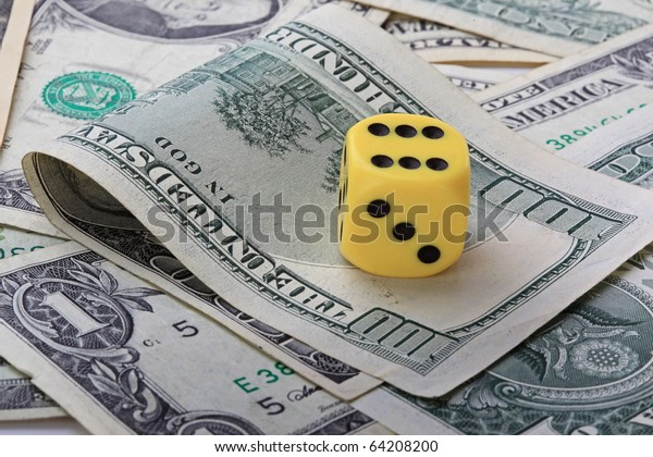 The concept photo of gambling. The closeup of money banknotes and a dice.