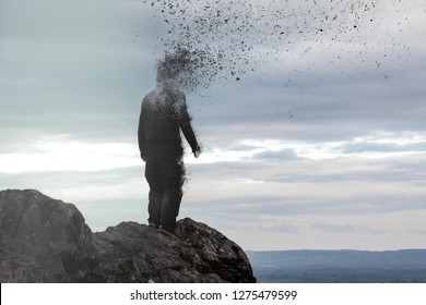 A concept photo of a hooded figure standing on a hill as his head  disintegrates into the air.
