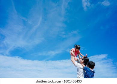 Concept photo of Malaysia Independent Day. Father holding his daughter and son while flying Malaysian flag with a copy space.