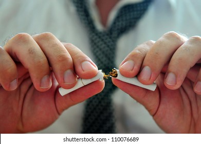 Concept photo of a man quitting smoking by breaking a cigarette.