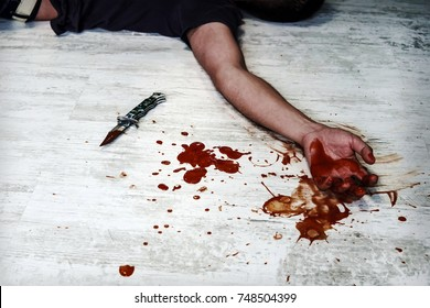 Concept photo of murder and crime. young man's body on the floor with bloody wounds and blood on his arm and close a folding knife with drops of blood. Suicide.