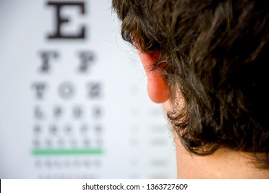Concept photo of myopia or nearsightedness as diseases of eye and the optical system. In the background blurry fuzzy table for testing visual acuity, in the front - head of the person in focus closeup