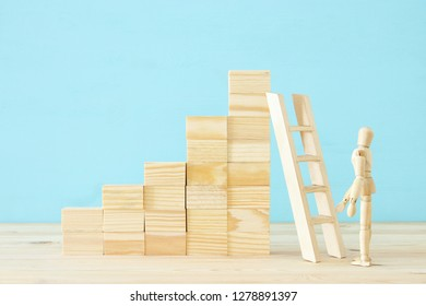 concept photo of obstacles overcoming, wooden dummy looking at a barrier and thinking about solution