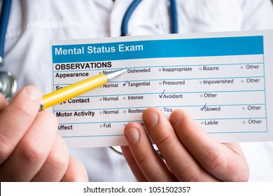 Concept photo psychiatric examination, assessment or consultation. Psychiatrist holds conclusion mental status exam and handle on it in foreground. In background is doctor himself in medical lab coat