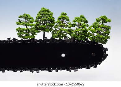 Concept photo referring to environment protection and wood cutting with chainsaw blade and small trees on it.
