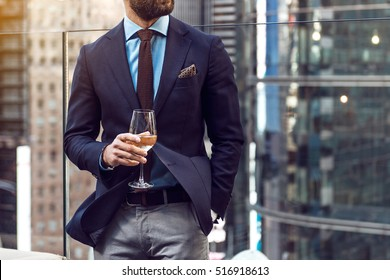 Concept photo of rich people luxury life. Adult successful elegant businessman wearing suit and drinking wine on the rooftop in luxury penthouse in New York City.