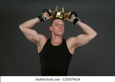 Concept photo of selfish and arrogant winner fighter or boxer man that is holding a golden crown above his head isolated on gray background.
