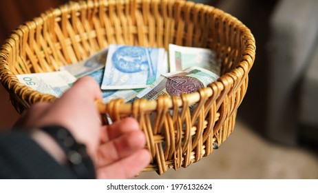 concept photo showing a donation tray in a church. Collecting tributes during the Holy Mass. Controversy over church finances