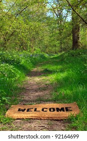 Concept photo of a Welcome doormat on a woodland footpath during springtime in vertical format.