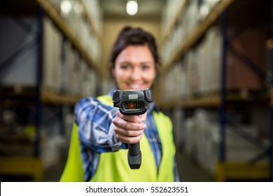 Concept photo of a woman scanning a bar code with a hand scanner in a warehouse. Traceability, FIFO, LIFO, just in time concept photo.