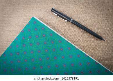 Concept photo of Writing - a black pen next to a colorful notebook with south african shweshwe patter on a cream textured background