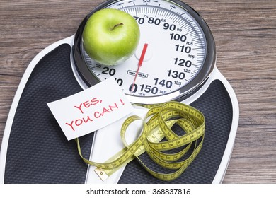 Concept photography for healthy life with apple, bathroom scales and tape measure
