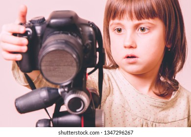 Concept: photography is my passio. Little cute child girl photographer is taking a photo.