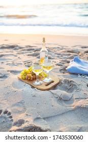 The concept of a picnic is wine, plaid, glasses, fruits. Sand, sea, sunrise. Close-up.
