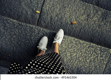 Concept picture of legs walking, vintage toned color image.Selfie of feet in white sneaker shoes and long skirt on rock stairs background, top view.
