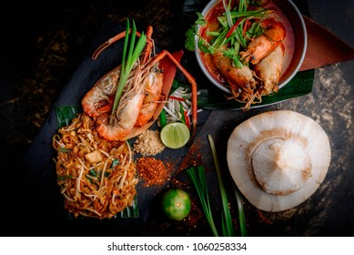 Concept pictures of famouse Thai dishes, Tom Yum Kung, Phad Thai and coconut. Beautiful presentation on black stone and black background.