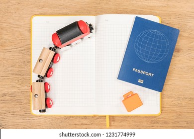 Concept planning an overseas trip by train with a toy train, suitcase and passport on diary