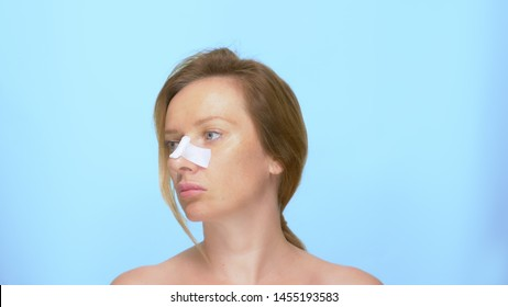 The concept of plastic surgery. rhinoplasty portrait of a woman with a bandage on the nose after the rhinoplasty procedure. on blue background
