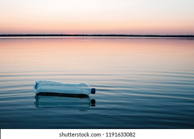 Concept of pollution, creative background. A plastic bottle floating in the ocean, non-decomposable plastic, pollution of the environment.