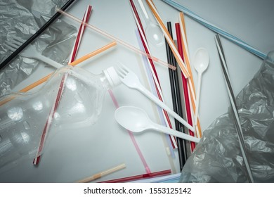 The concept of pollution plastic and polyethylene environment. Cellophane bag, plastic bottle, disposable forks and spoons, cocktail tubes on gray background. Top view