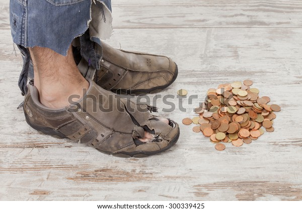 concept of a poor person and his feet with some coins