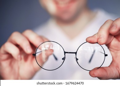The concept of poor vision. Hold a contact lens and glasses in hand. Poster for advertising glasses and lenses.