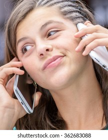 concept portrait of addict young girl having an animated conversation with a phone in each hand