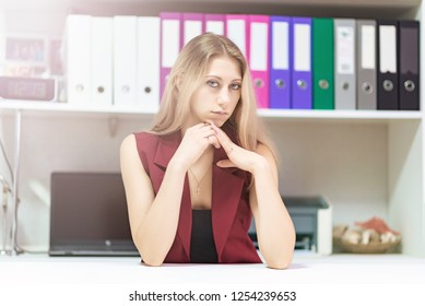 Concept portrait of a beautiful blonde girl secretary manager smiling working in an office.
