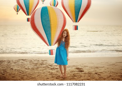 Concept portrait of beautiful little child girl with red hair and freckles standing on a beach with colourful hot air balloon