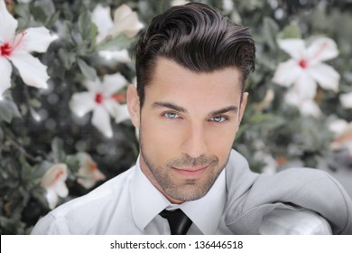 Concept portrait of a beautiful young man against background of flowers