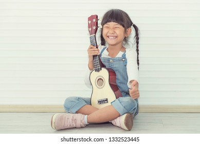 Concept portrait children of learning with the music activity. Adorable cutest girl so happiness & trying to play ukulele in the living room