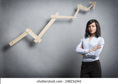 Concept: Positive business outlook. Smiling confident businesswoman in front of business graph with upward trend, isolated on grey background
