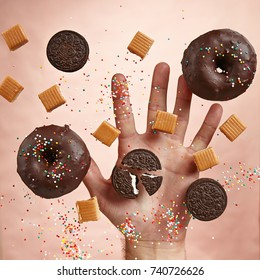 Concept poster. Sweet donuts with chocolate icing, chocolate cookies, toffee on pastel background with an open hand.