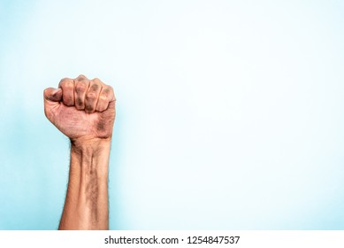 Concept of power, dictator, bossy or freedom. Male dirty fist, hand up, to left side on blue background
