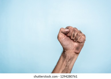 Concept of power, dictator, bossy or freedom. Male dirty fist hand on blue background