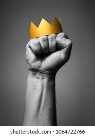 Concept of power. Golden crown on a man's fist. Black and white.