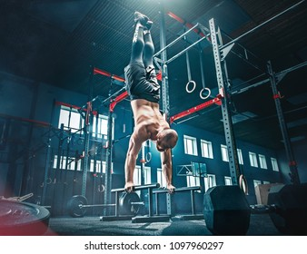 Concept: power, strength, healthy lifestyle, sport. Powerful attractive muscular man CrossFit trainer do pull ups during workout at the gym on beams