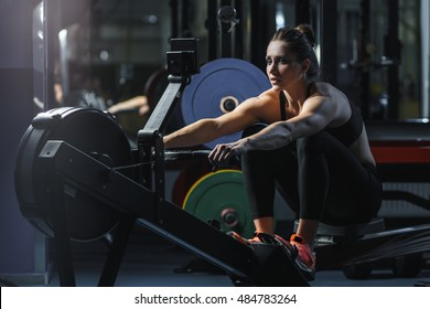 Concept: power, strength, healthy lifestyle, sport. Powerful attractive muscular woman CrossFit trainer do workout on indoor rower at the gym