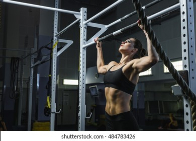 Concept: power, strength, healthy lifestyle, sport. Powerful attractive muscular woman CrossFit trainer do pull ups during workout at the gym