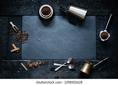 Concept - preparing of coffee. Coffee cup, mocha, coffee maker, roasted beans, spoons, turkisch cezve, biscuits and cardamom. Coffee background on a stone and black wood.