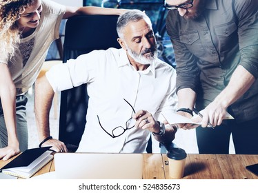 Concept of presentation new idea business project.Adult businessman discussing ideas with account director and creative manager in modern office.Horizontal close-up, blurred background