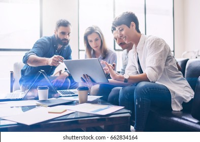 Concept of presentation new startup project.Group of young coworkers discussing ideas with each other in modern office.Business people using electronic devices.Horizontal, blurred background