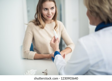 Concept of professional consultation and remedy. Waist up portrait of female doctor showing nasal drops to smiling young lady in clinic