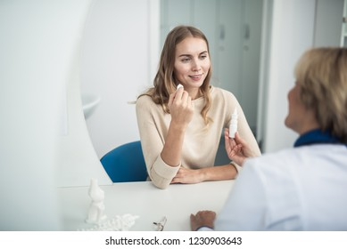 Concept of professional consultation and remedy. Waist up portrait of female doctor giving nasal drops to young lady with running nose