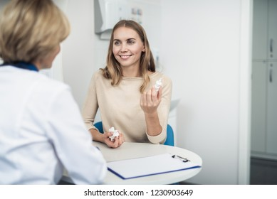 Concept of professional consultation and remedy. Waist up portrait of lady doctor and young female patient with running nose holding nasal drops. Copy space on right