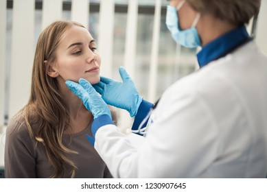 Concept of professional consultation in therapist system. Close up portrait of doctor woman examining tonsils of smiling young lady in medical office