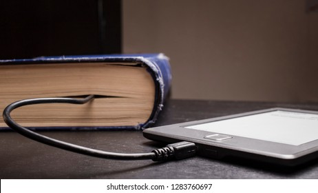 concept of progress and compactness, eBook connected to the old thick blue book with a cable, and download information from there